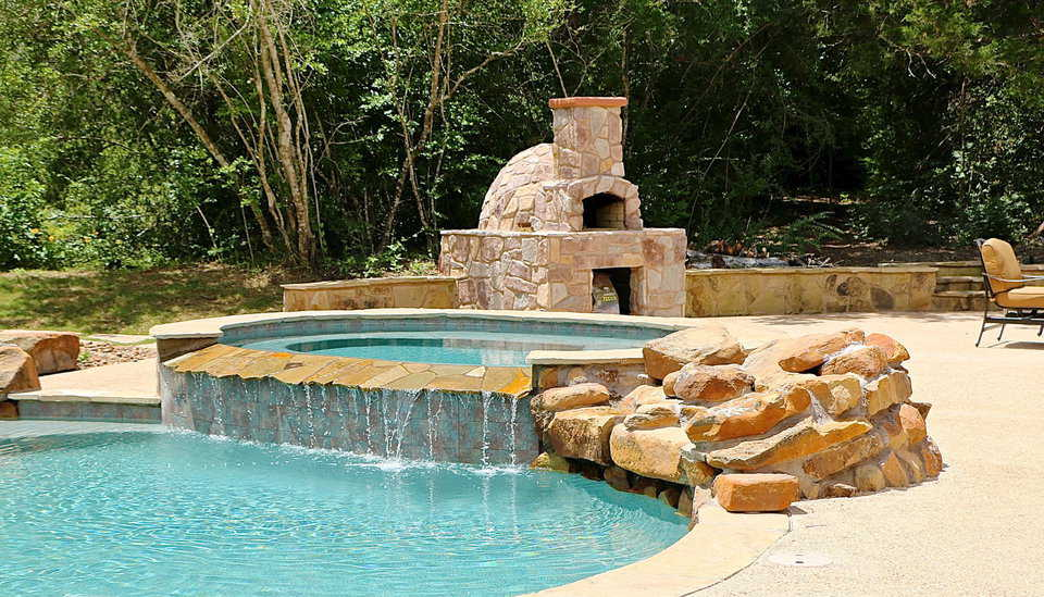 Near the swimming pool in the Whiteacre's backyard is a pizza oven covered in rock to match their Monolithic Dome Home.