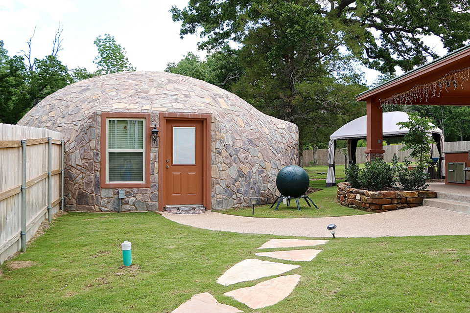 A sectioned stone walk leads to the Monolithic Dome guest house which is next to a composting ball. From there, guests can make their way up to the covered grilling area and toward the pool.