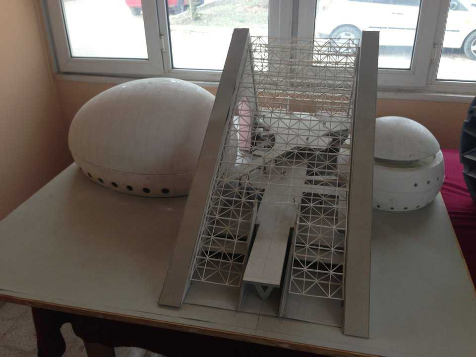 A model of the finished exterior of the colossal ellipsoid dome and its impressive spherical counterpart, juxtaposed with the vaulted triangular foyer, under construction in downtown Ankara, Turkey on Ataturk Boulevard.