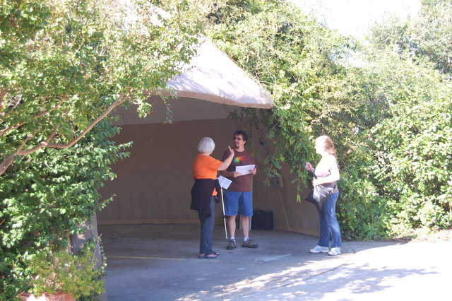 Three guests, two from Arkansas, discuss the vine-covered EcoShell garage.